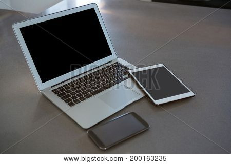 Laptop with digital tablet and mobile phone on kitchen counter at home