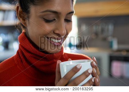 Smiling young woman having coffee in kitchen at home
