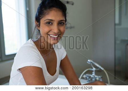 Portrait of smiling woman sitting on bathtub in bathroom
