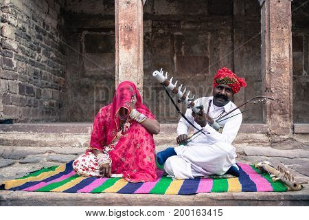 JODHPUR RAJASTHAN INDIA - MARCH 05 2016: Horizontal picture of indian couple playing local music inside Mehrangarh Fort in Jodhpur the blue city of Rajasthan in India.