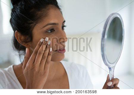 Close-up of young woman holding hand mirror at home