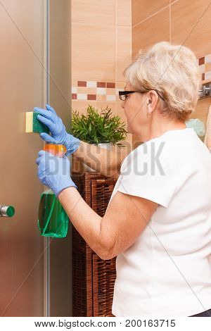 Senior Woman Cleaning Glass Shower Door Using Sponge And Detergent, Household Duties Concept