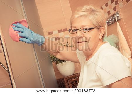 Elderly Senior Woman Using Pink Microfiber Cloth And Cleaning Shower In Bathroom, Household Duties C
