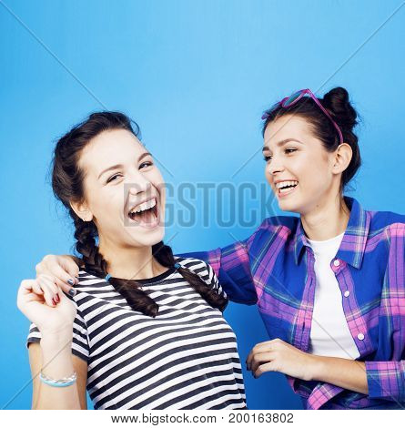 best friends teenage school girls together having fun, posing on blue background, besties happy smiling, lifestyle people concept close up
