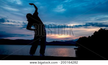 The silhouette of a woman exercising on the edge of a reservoir behind the mountain