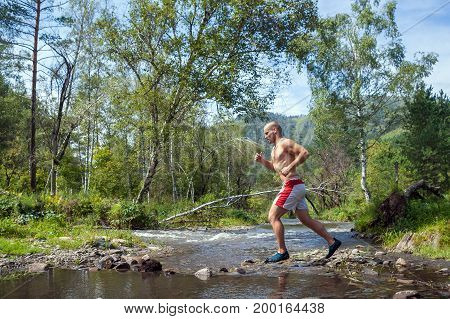 A young sporty bald man with a naked torso and short white shorts running down a mountain river on a summer day against the background of the Altai Mountain. Runner athlete runs over the stones