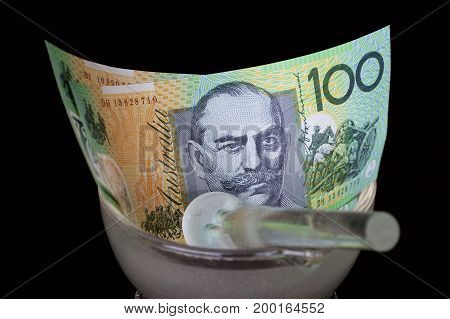 Australian hundred dollar note in a glass mortar and pestle.