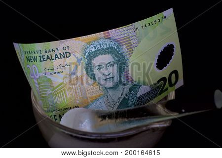 New Zealand twenty dollar note in a glass mortar and pestle.