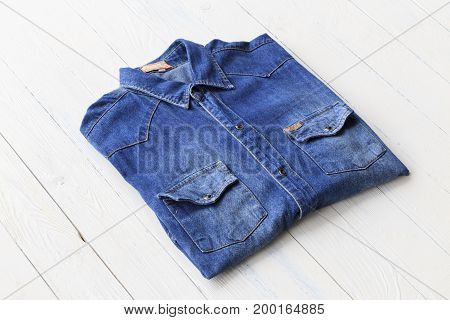 Top view close up blue denim shirt jeans put on white wooden tabletop