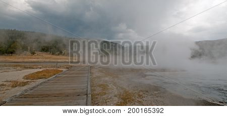 Elevated Boardwalk around Hot Cascades hot spring geyser and Hot Lake in the Lower Geyser Basin in Yellowstone National Park in Wyoming United States