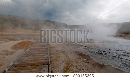 Boardwalk around Hot Cascades hot spring geyser and Hot Lake in the Lower Geyser Basin in Yellowstone National Park in Wyoming United States