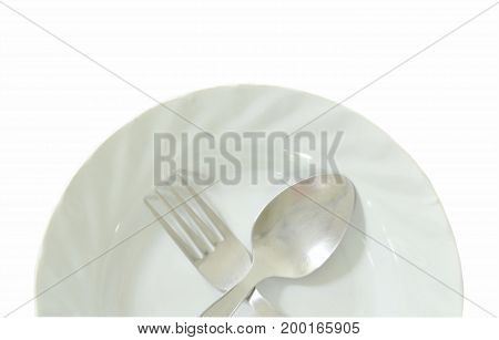 spoon and fork crossing on plate in white background