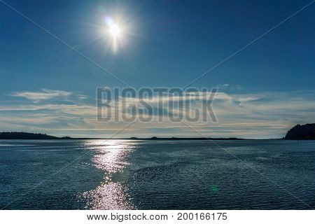 Blue Skyline With Sun And Clouds Over The Ocean Water At Summer Time.