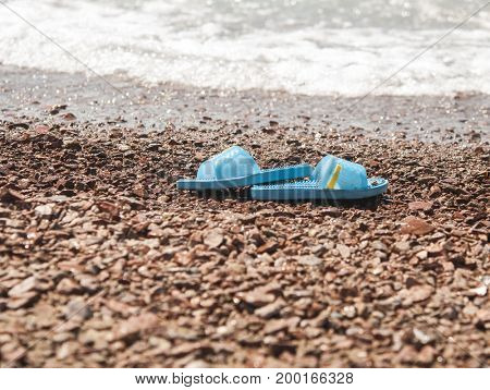 blue slippers on the sand beach with relaxing waves