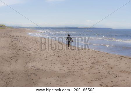 Young boy running fast down an empty beach beside glittering ocean waves in the sunlight freedom vacation summer and activity concepts background with space for text