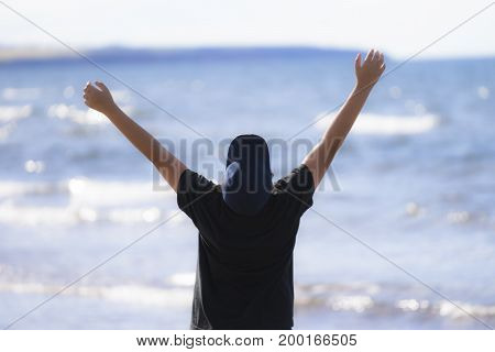 Boy raising his arms in joy and praise at seeing the ocean dark baseball cap and tshirt body in silhouette bright water soft focus