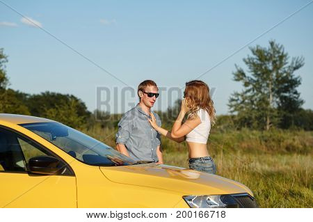Couple in love. Road Trip. The guy is standing next to a friend. Girl talking on his cell phone while standing at the machine.
