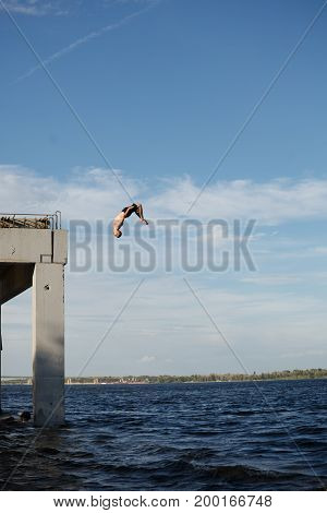 A man is jumping into the sea from a high pier. Adrenaline and extreme sports. Back flip jump.