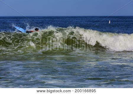 Surfer riding large ocean wave at the day time Surfing swims large waves in the ocean