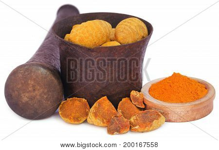 Whole and ground turmeric in bowl with mortar and pestle