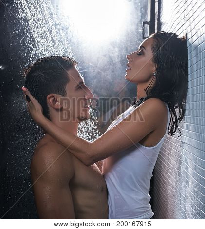 Young nude man and woman in white shirt sharing an intimate moment in shower