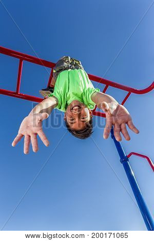 A happy young boy hangs upside down from the monkey bars.