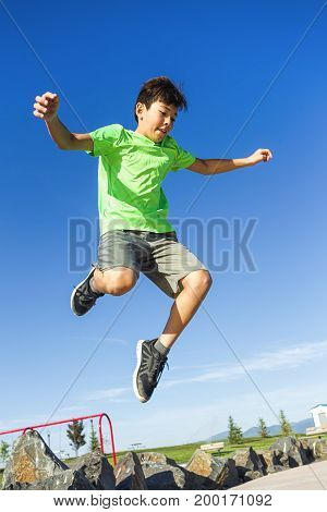 Boy leaping in the air on a bright summer day.
