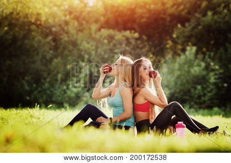 Group portrait of two white Caucasian girls sit together after training fitness, yoga, eating apple food. Concept love of friendship, best friends forever, healthy, healthy food, sports diet.