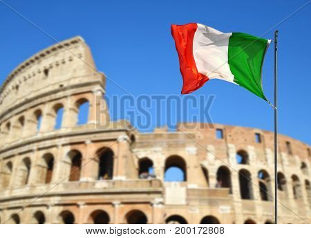 Italian flag with Flavian Amphitheatre or Colosseum in the background. Rome, Italy