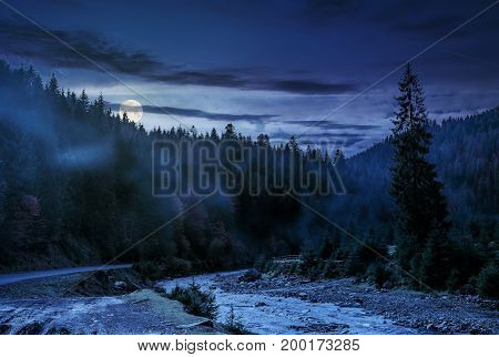 valley with river in foggy forest. Spectacular autumnal landscape in mountains at night in full moon light