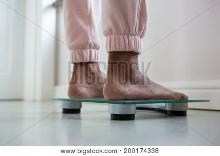 Low section of woman standing on bathroom scale
