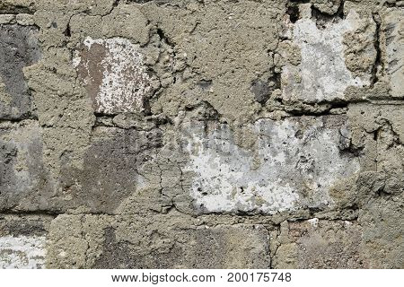 Old grunge brick wall with remnants of plaster. Brickwork close-up. Background, texture