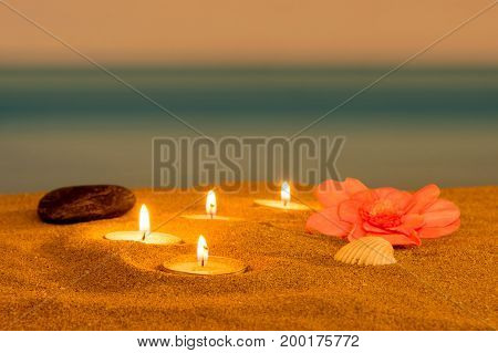 Candle on the beach relaxation concept, in night