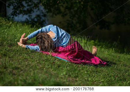 Caucasian woman practices yoga asana in park in the morning.