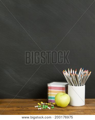 School supplies with stack of pencil and an apple on blackboard background with copyspace for your text design. Back to school concept