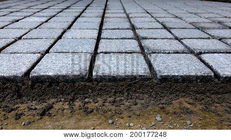 Cobblestone tiles in flooring process in construction site, selective focus.