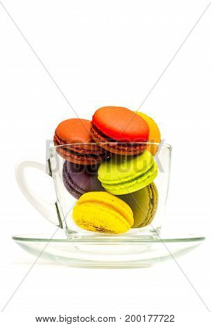 Colorful sweet macarons in a glass on white background