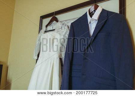 Bride dress and groom suit in dressing room indoors hang on picture
