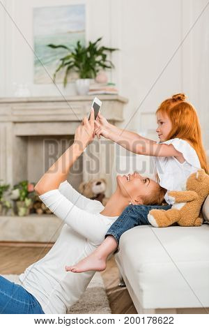 side view of mother and little daughter using tablet together at home