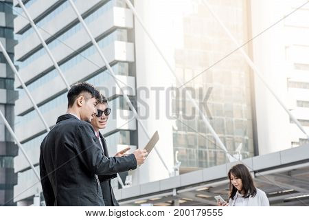 Happy Asian business people holding tablet discussing business project. Co-worker businessman standing outside office in city with blurred businesswoman using smartphone. Background or copy space.
