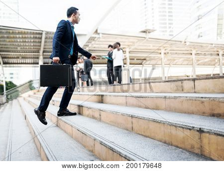 Lifestyle of young Asian businessman holding black business briefcase walking up the stair with blurred business people background outside office in the city after workout. Business concept copy space