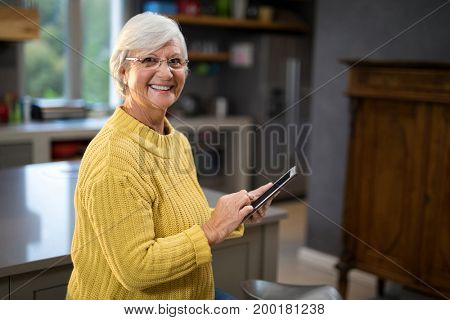 Senior women holding a tablet while standing in the kitchen