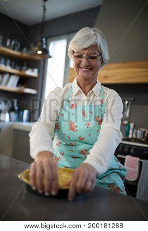 Smiling senior woman having tart in kitchen