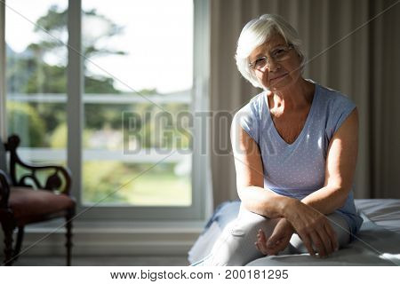 Portrait of senior sitting on bed in bedroom at home