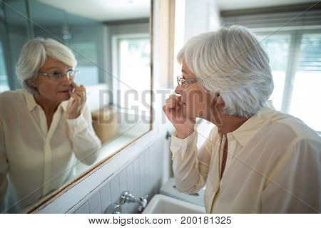 Senior woman checking her skin in mirror at bathroom
