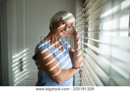 Portrait of tense senior woman standing near window in bedroom at home