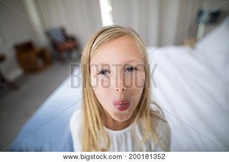 Portrait of girl pouting in bedroom at home