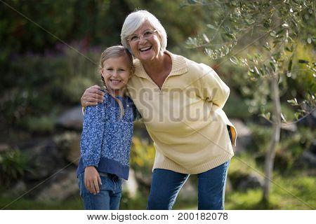 Portrait of smiling granddaughter and grandmother standing together in garden on a sunny day