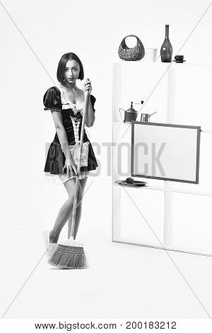 woman in sexy maid servant costume posing with sweep broom near kitchenware on shelves isolated on white background black and white