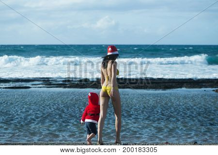 Christmas and new year celebration. Woman and child walking on sea beach. Mothers day and family love. Girl in swim suit and boy wearing santa costume. Winter holidays concept.
